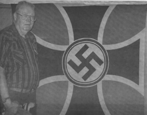 Ross Neale displays a German flag that was liberated from Rommel's headquarters in Normandy in 1944.